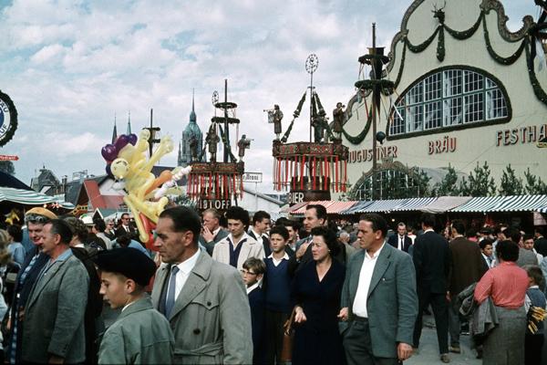Besucher auf dem Oktoberfest in München mit Augustinerbräuzelt im Hintergrund.