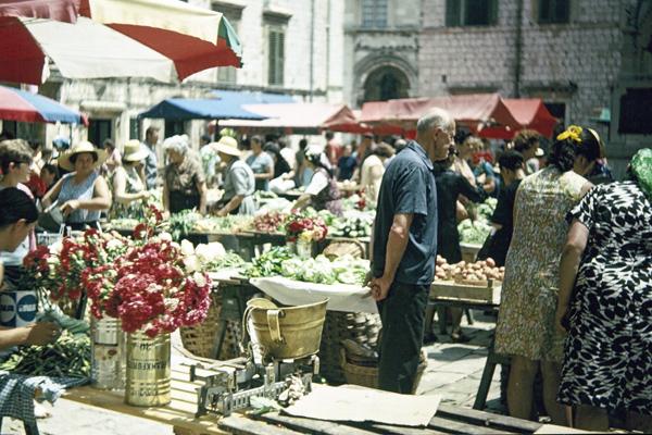 Auf dem Wochenmarkt am Stadtplatz von Dubrovnik reicht das Spektrum der angebotenen Waren von frischen Schnittblumen bis hin zu frischem Obst und Gemüse. Das Wirtschaftswunder in Deutschland ist auch hier spürbar.
