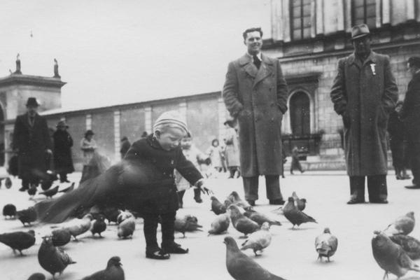 Ein kleiner Junge spielt mit Tauben auf dem Odeonsplatz in München. Im Hintergrund sehen ihm Passanten zu.
