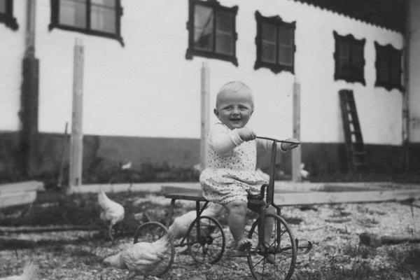 Ein kleiner Junge fährt auf einem Metall- oder Eisendreirad über einen Hof. Um ihn herum picken Hühner auf dem Boden.