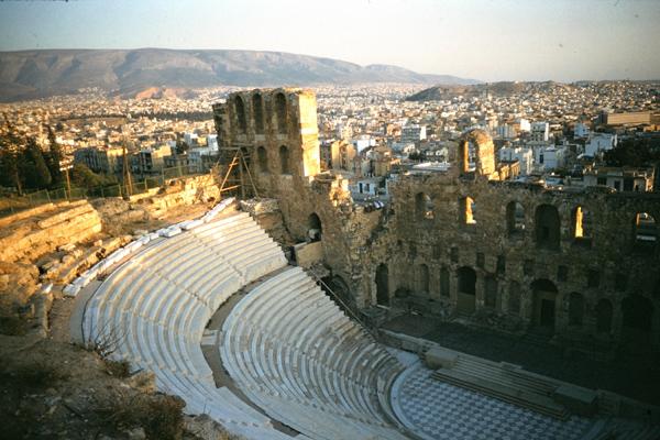 Der Odeon des Herodes Atticus bei Sonnenuntergang mit der Stadt Athen im Hintergrund.