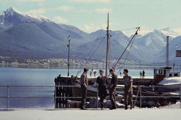 Männer stehen vor einem Fischerboot im Hafen von Andalsnes im Romsdalfjord.