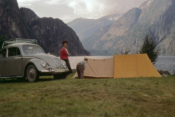 Ein Mann und eine Frau bauen neben einem VW-Käfer ein Zelt an einem Fjord in Norwegen auf.