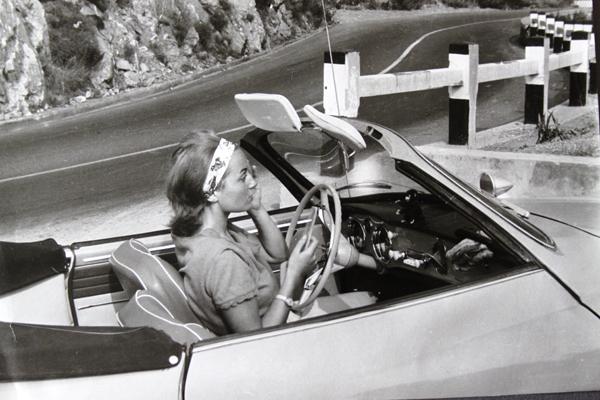 Eine junge Frau betrachtet sich im Rückspiegel eines Karmann-Ghia Cabrios an einer Küstenstraße an der Côte d'Azur.