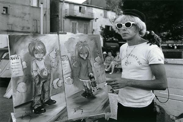 Ein Straßenkünstler mit seinen Bildern an der Hafenmole von St. Tropez.