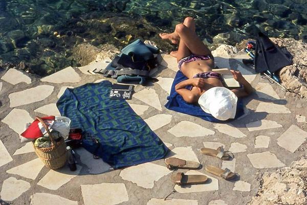 Frau im Bikini liegt an der Adria in Hvar und liest ein Buch.