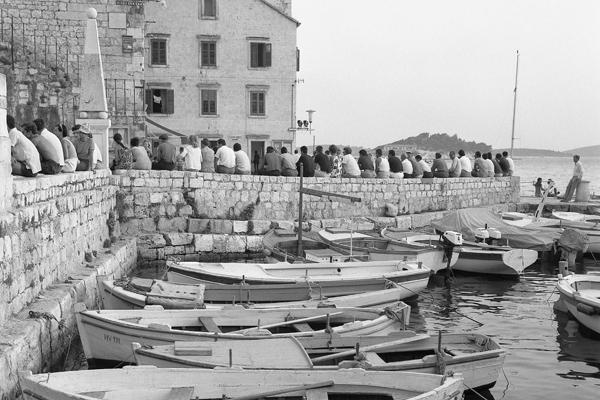Ruderboote und Menschen die auf einer Mauer am Hafen von Hvar sitzen.