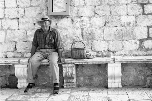 Mann mit Hut und Korb sitzt auf einer Bank in Hvar und verkauft etwas in kleine Flaschen.