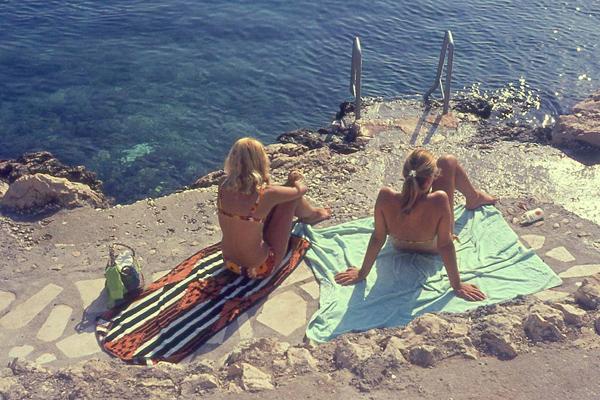 Frauen in Bikinis sonnen sich auf Handtüchern an einem Strand in Hvar.