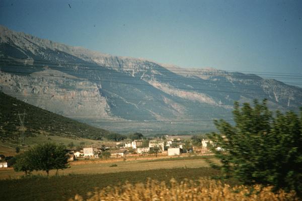 Blick über ein Dorf und Felder auf das Parnass-Gebirge in Zentralgriechenland.