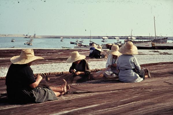 Frauen mit Hüten flicken Netze im Hafen von Vinaroz zwischen Valencia und Tortosa.
