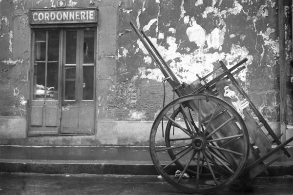 Die Fassade einer Schuhmacherei (Cordonnerie) auf der Binneninsel Ile de la Cite in Paris. Daneben ein Handkarren.