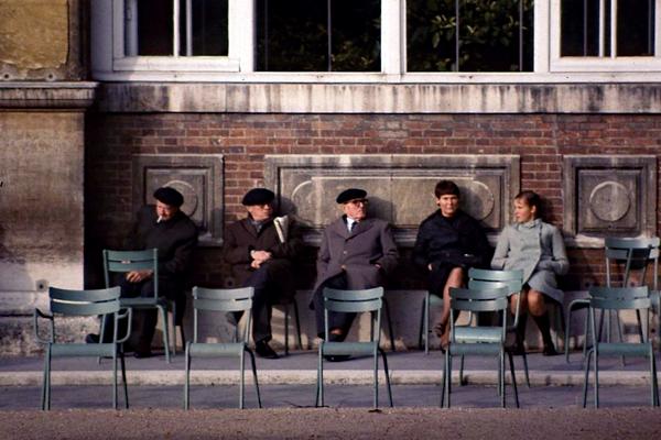 Männer mit Baskenmützen und Frauen mit Mantel sitzen auf Stühlen im Jardin du Luxembourg in Paris.