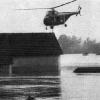 Rettungshubschrauber über überflutetem Dorf