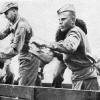 Amerikanischer und sowjetischer Soldat dichten einen Damm ab