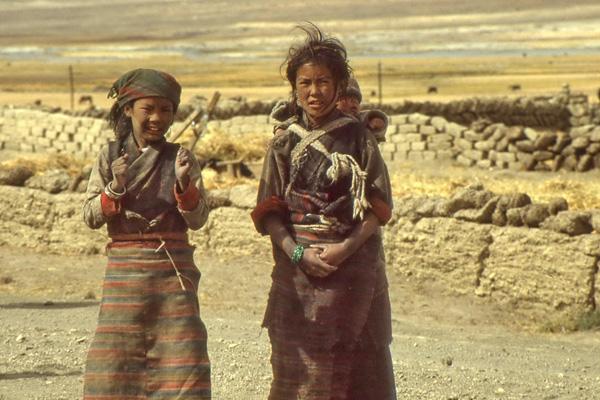 Zwei tibetische Mädchen auf einer Straße. Das Mädchen rechts im Bild hat ein Kind in einem Tragetuch auf dem Rücken. Im Hintergrund Steinmauern.