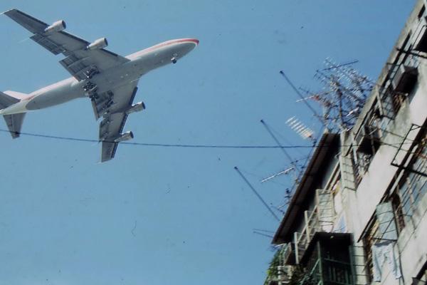 Ein Flugzeug beim Landeanflug über Hongkong. Rechts im Bild ein Wohngebäude.