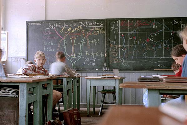 Klassenzimmer mit Schülern und Tafel.