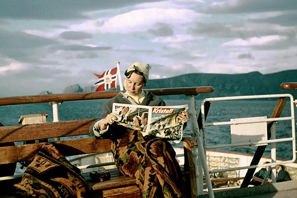 Eine Frau liest die Zeitschrift 'Kristall' auf einem norwegischen Postschiff. Im Hintergrund die Postflagge Norwegens.
