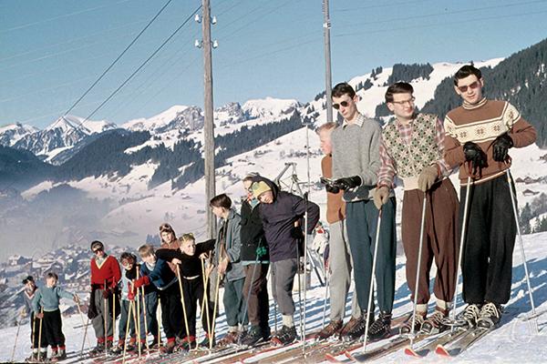Skikurs in Tirol wartet in einer Reihe aufgestellt am Hang.