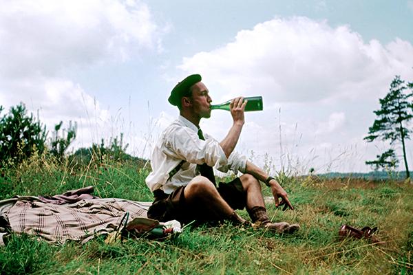 Mann sitzt auf einer Decke und trinkt aus einer Flasche.