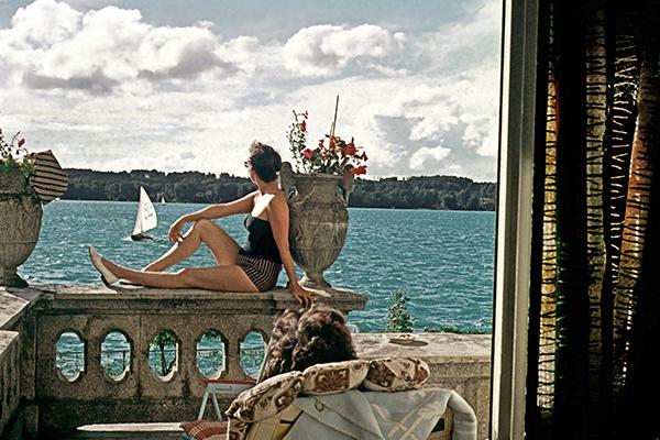 Frau geniesst das Sonnenbad auf Veranda mit Blick auf den Starnberger See