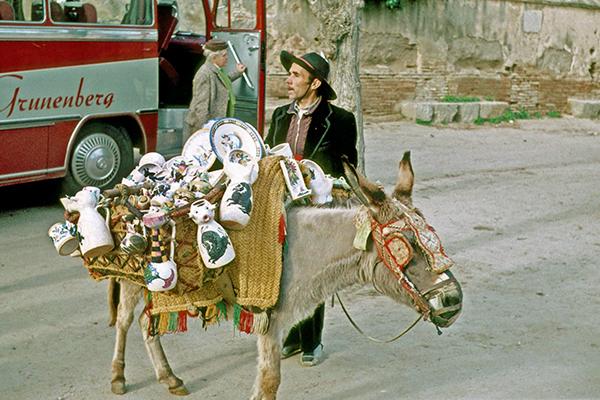 Souvenirverkäufer mit bepacktem Esel in einem Span. Dorf