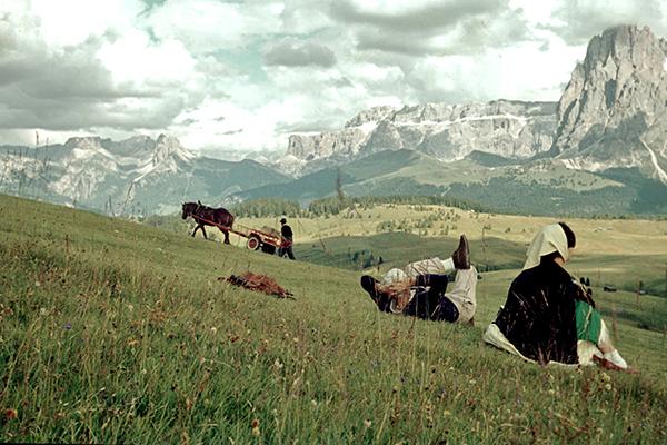 Ein Paar auf einer Almwiese vor den Dolomiten. Im Hintergrund ein Mann mit einem Pferdewagen.