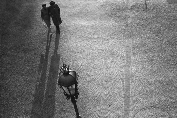 Ein Mann besteigt die Treppe zum Friedensengel in München. Im Hintergrund zwei Frauen die lange Schatten werfen.