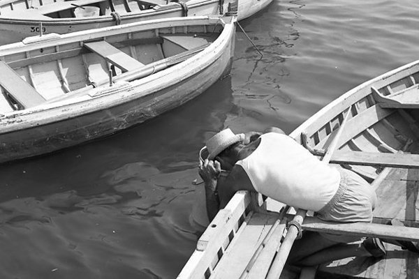 Ein Fischer in Italien und lehnt sich über ein Boot zum Wasser hin.