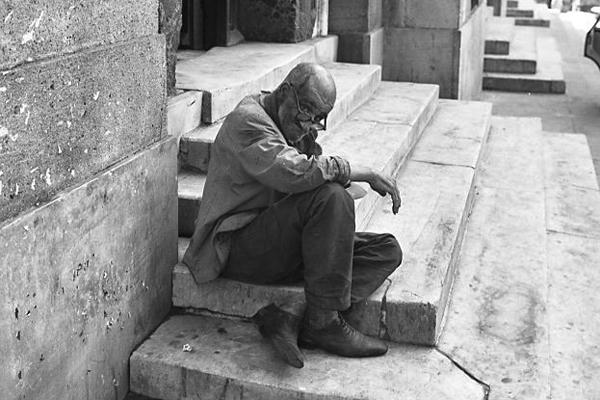 Ein älterer Herr sitzt auf einer Treppe in Italien und pausiert.
