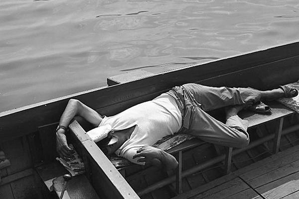 Ein Mann schläft auf einem Boot in Italien.