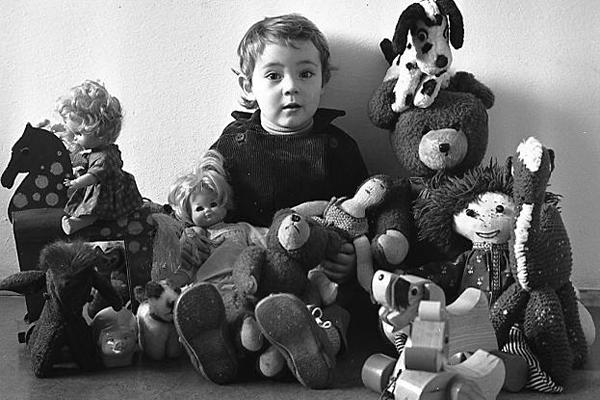 Portraitaufnahme von einem kleinen Kind mit Puppen und Kuscheltieren