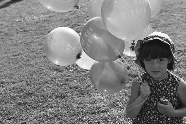 Ein Mädchen mit Luftballons auf einem Kinderfest in Deutschland.