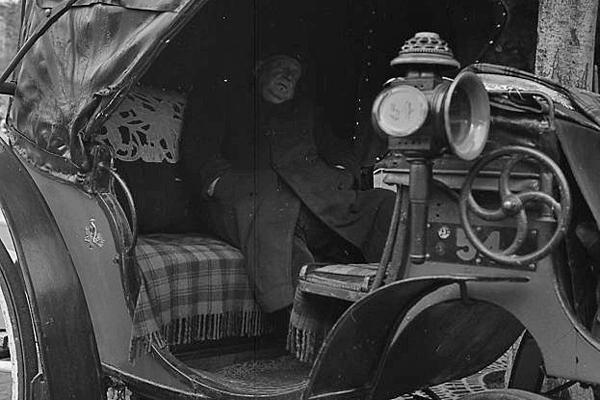 Ein Mann sitzt in einer Pferdekutsche und schläft in Paris.