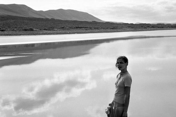 Frau steht im Wasser am Strand von Lanzarote.