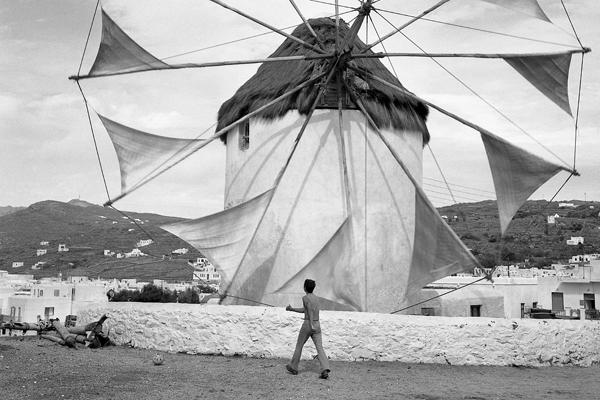 Windmühle auf der Insel Mykonos und im Vordergrund ein Junge.