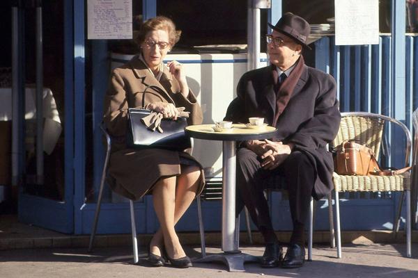 Dame mit Handtasche und Handschuhen und ein Herr mit Hut und Mantel trinken Kaffee im Cafe a la Deux in Clignancourt in Paris.