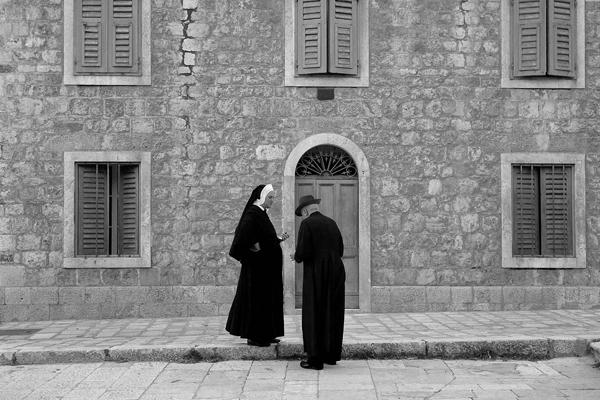 Nonne und Pfarrer unterhalten sich vor einem Haus in Hvar.