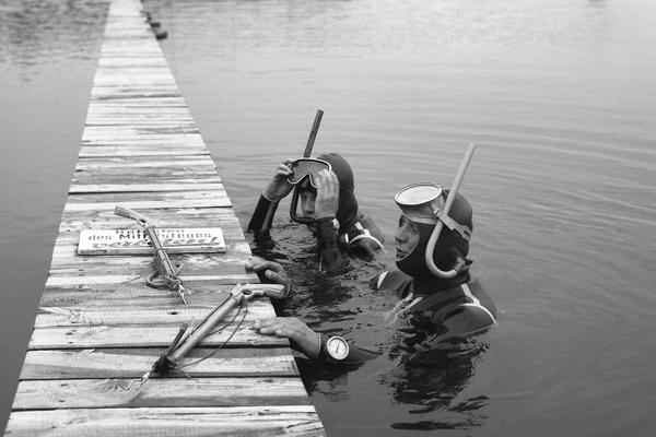Taucher am Petersdorfer See in Petersdorf. Bild zeigt Männer im Wasser an einem Steg mit Harpune.