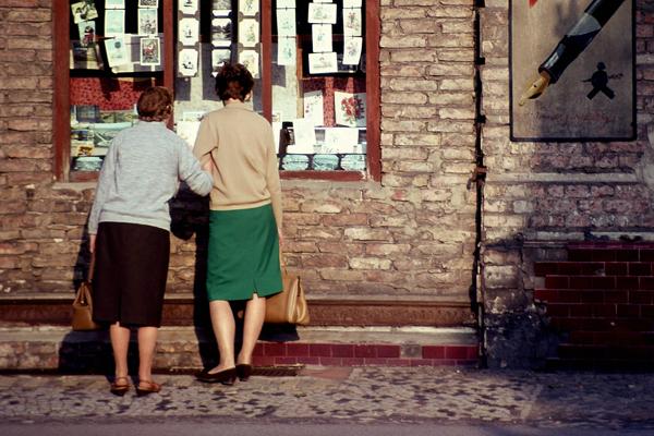 Frauen am Winterfeldtplatz in Berlin betrachten Postkarten in einer Vitrine.