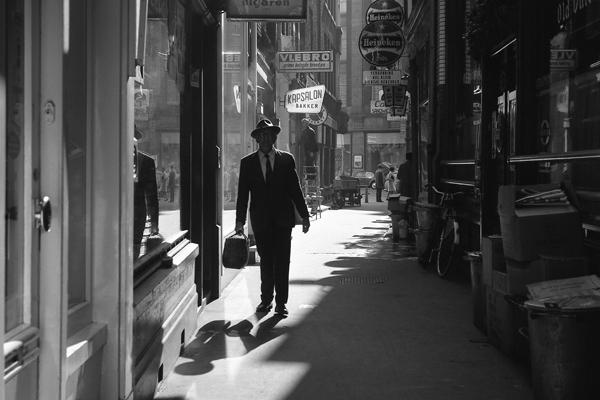 Mann mit Anzug, Hut und Koffer und Reklame (Willem II, Old Ducht Inn, Heineken, Kapsaloin Bakker, Vlebro) in einer Gasse in der Altstadt von Amsterdam.