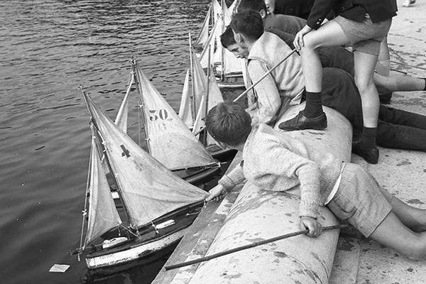 Kinder lassen im Jardin de Tuileries Spielzeug-Segelschiffe fahren.