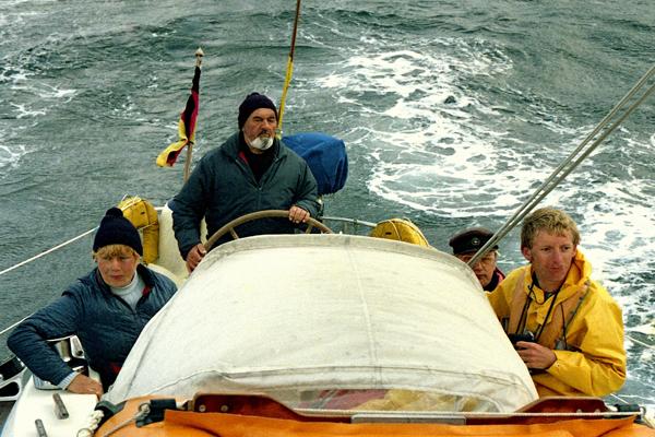 Vier Menschen beim Segeln in der Nordsee. Es regnet.