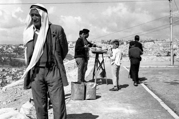 Ein Mann am Ölberg in Jerusalem. Er trägt eine Kufiya. Im Hintergrund verkaufen Jugendliche Brot.