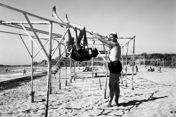 Zwei Männer turnen an einem Metallkonstrukt am Strand vom Kibbuz Gesher Haziv in Israel.