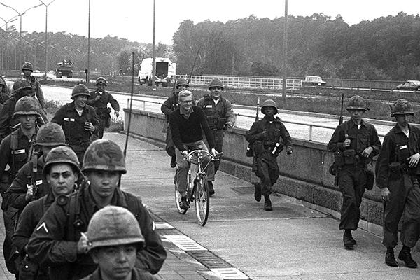 Ein ziviler Fahrradfahrer f‰hrt vorbei an US-Soldaten im Einsatz in Berlin.