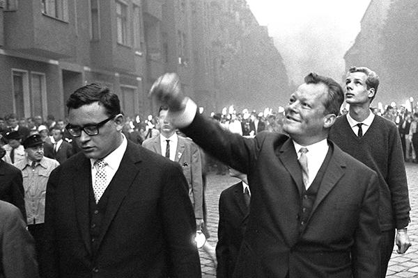 Der Westberliner B¸rgermeister Willy Brandt hebt w‰hrend einer Kundgebung anl‰sslich des ersten Jahrestages des Mauerbaus in Kreuzberg neben Klaus Sch¸tz die Hand.
