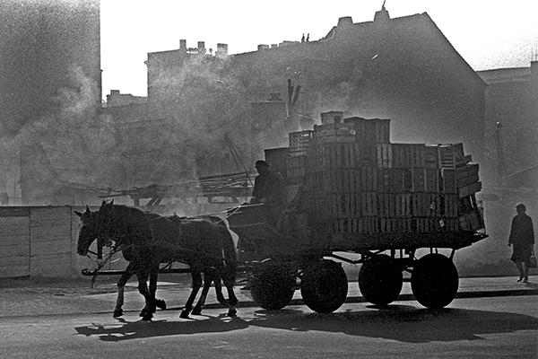 Ein schwer beladener Karren wird von Pferden gezogen in Ost-Berlin.
