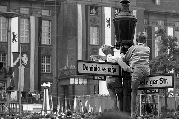 Zwie Jungen klettern auf Stra?enschilder, um die Kungebung und die Demonstration zum ersten Jahrestag des Mauerbaus vor dem Schˆneberger Rathaus in Berlin zu verfolgen.